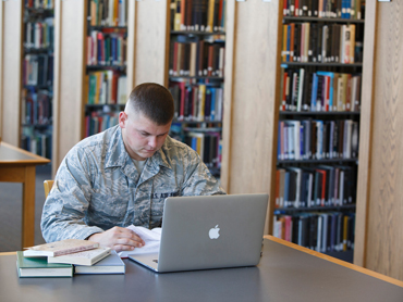 Military student working on a laptop in the library